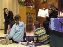 children sitting on mat while a story is read to them